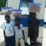 Three young children carrying food to sell at one of our bus stops