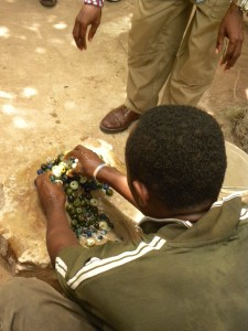 One of the men polishing beads with the water and dirt on the flat rock.