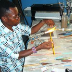 Cedi making a decorative glass bead by melting sticks of glass into designs